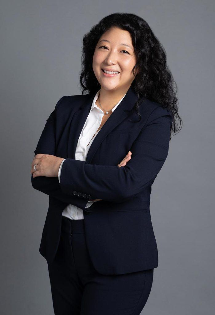 woman wearing dark suit and white shirt with curly long black hair smiling