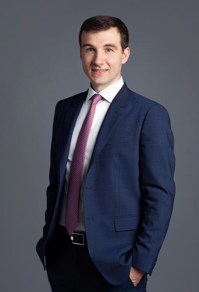 man wearing navy suit and pink tie with short brown hair